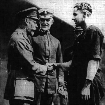 King George shakes hand with Lt. Mims, captain of the army team.  Admiral Sims looks on.