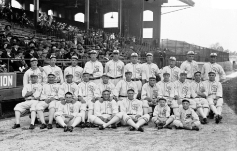 Group portrait of American League's Chicago White Sox baseball team posing in front of a section of the grandstands on the field at Comiskey Park, Chicago, Illinois, 1917.